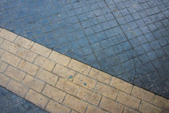 Marquage routier jaune raye plus de sur le trottoir gris de pavé rond Photo stock