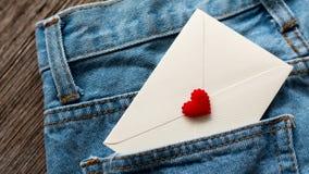 Marque avec des lettres le blanc dans la poche de jeans Photographie stock