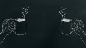 Marque la mano con tiza que dibuja una mano que sostiene la taza de café con vapor en tablero negro en el lado izquierdo y derech fotografía de archivo libre de regalías