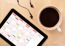 Marque o PC que mostra o calendário na tela com uma xícara de café em um d Imagem de Stock