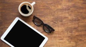 Marque o PC que olha como o ipad na tabela de madeira com café e vidros pretos, configuração lisa imagens de stock