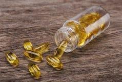 Marque sur tablette la vitamine E dans un réservoir en verre Huile de poisson Photos stock