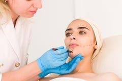 Marques de dessin de docteur sur le visage femelle photographie stock