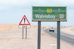 Marqueur rouillé et avertissement de distance contre le sable sur la route Photographie stock