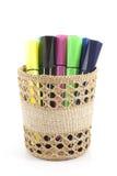 Marqueurs colorés dans le panier sur le fond blanc Image stock