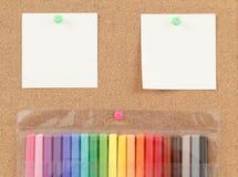 Marqueurs de couleur avec des notes sur le panneau de liège Image stock