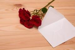 Marquez avec des lettres et un bouquet des roses rouges sur le fond en bois Photo libre de droits