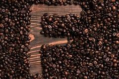 Marquez avec des lettres l'inscription de F avec le grain de café sur la table en bois Photos stock