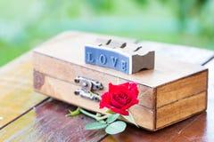 Marquez avec des lettres la rose d'amour et de rouge sur une boîte en bois Image libre de droits