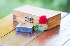 Marquez avec des lettres la rose d'amour et de rouge sur une boîte en bois Photo stock