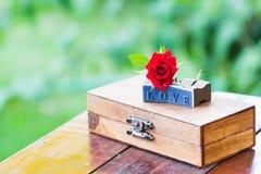 Marquez avec des lettres la rose d'amour et de rouge sur une boîte en bois Photos stock