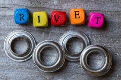 Marquez avec des lettres le cube et les rivets sur la visualisation en bois grise Photo stock