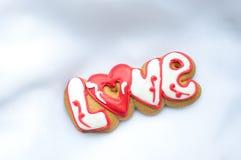 Marquez avec des lettres les biscuits pour le jour du ` s de Valentine ou pendant un jour du mariage sur le fond du tissu léger b Photographie stock libre de droits