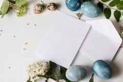 Marquez avec des lettres les oeufs décorés par Pâques vides et les fleurs blanches fraîches Images libres de droits