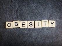 Marquez avec des lettres les tuiles sur l'obésité noire d'orthographe de fond d'ardoise image stock