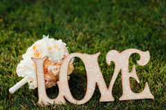 Marquez l'amour sur le fond d'un bouquet de mariage Photographie stock libre de droits