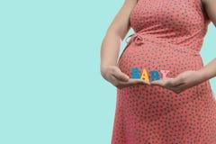 Marquez le bébé dans les mains d'une femme enceinte Photos libres de droits