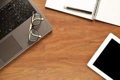 Marquez sur tablette et d'autres articles sur un bureau en bois Image stock