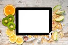 Marquez sur tablette l'ordinateur avec le fruit et une bande de mesure pour la perte de poids photo libre de droits