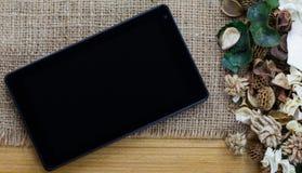 Marquez sur tablette l'ordinateur (PC de comprimé) et les fleurs sèches Photographie stock libre de droits