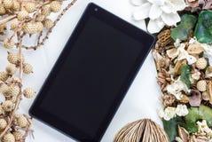 Marquez sur tablette l'ordinateur (PC de comprimé) et les fleurs sèches Images stock