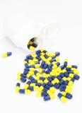 Marquez sur tablette la bouteille avec la médecine se renversant hors de elle sur le blanc Photos libres de droits