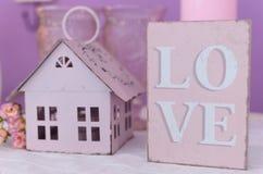 Marquez sur tablette le ` d'amour de ` et un chandelier sous forme de maison Photo libre de droits