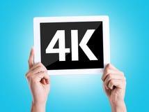 Marquez sur tablette le PC avec le texte 4K avec le fond bleu Photos libres de droits