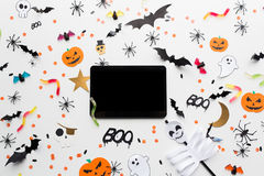 Marquez sur tablette le PC, les décorations de partie de Halloween et les sucreries Photographie stock