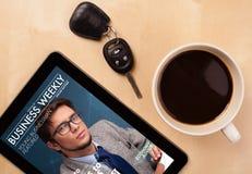 Marquez sur tablette le PC montrant la magazine sur l'écran avec une tasse de café sur un d Photographie stock