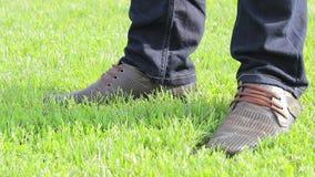 Marrón de las botas en hierba verde almacen de metraje de vídeo