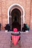 Marrakesh Maroko, Marzec, - 13, 2018: Mężczyzna w wózku inwalidzkim czeka przy wejściem Koutoubia meczet dla someone pomagać on obrazy royalty free