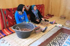 Ladies working to grind argan nuts to make oil, butters and othe Royalty Free Stock Photo