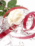 Marriage 060. White Rose, red ribbon, wedding rings and tinsel on a white background Royalty Free Stock Photos