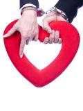 Marriage. Two handcuffed hands are holding the same heart. and emphasizing a compulsory marriage Royalty Free Stock Photography