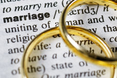 Marriage. Two wedding rings next to the word marriage on a english dictionary royalty free stock photography