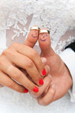 Marriage. Abstract image, concept with thumbs with painted smiles and wedding rings put on stock photography