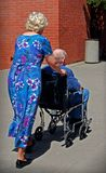 Marriage. Elderly man in a wheelchair being pushed by his wife dressed up for summer Royalty Free Stock Image