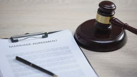 Marriage agreement on table, gavel striking on sound block, marital contract. Stock footage stock video footage