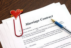 Marriage contract with pen on wooden table Stock Photos