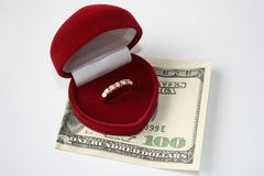 Marriage of convenience. Ring in a box as a heart, and one hundred dollars Royalty Free Stock Photos
