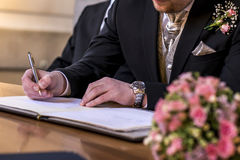 Marriage elegant groom signing german wedding register holding pen and official document couple Royalty Free Stock Photos