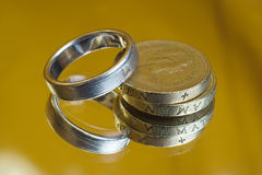 Marriage expense. Coins and wedding ring, to represent the costs and expenses involved in marriage Stock Photos
