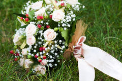 Marriage favours. Bouquet of the bride from beige roses Stock Photos