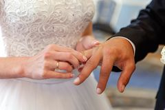The bride wears a ring to the groom stock photo