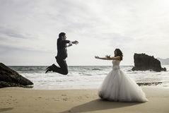 Marriage jumping beach. Marriage bridal dresses beach couple in love stock photos