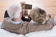 Marriage looking at photos. Senior marriage sitting on the sofa and looking at old photos Royalty Free Stock Photos