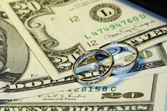 Marriage and Money. Close up of two marriage rings and U.S. dollars stock images