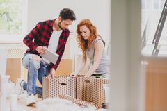 Marriage packing stuff into carton boxes while moving-out to new house. Concept royalty free stock photos