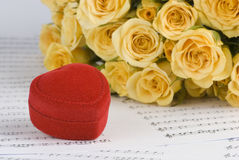 Marriage proposal. Yellow roses and a box holding wedding rings with musical background stock images